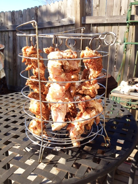 Wings suspendend in the basket, note one skewer has no seasonings.
